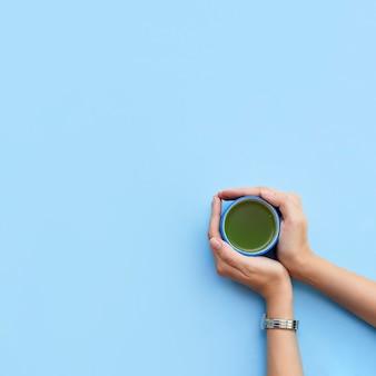 As mãos da mulher seguram uma xícara de chá matcha em um fundo azul