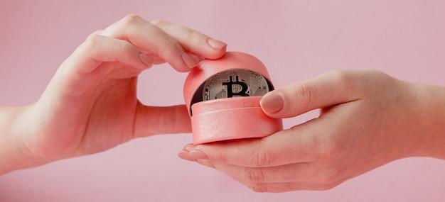 As mãos da mulher segurando bitcoin em caixa de presente rosa em uma rosa, símbolo de dinheiro virtual.
