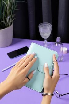 As mãos da mulher segurando o bloco de notas sobre a mesa violeta. acessórios femininos de verão