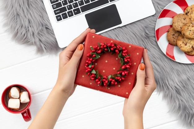 As mãos da mulher segurando um presente com chocolate e biscoitos em fundo peludo. compras online de natal trabalhando a partir do conceito de casa.