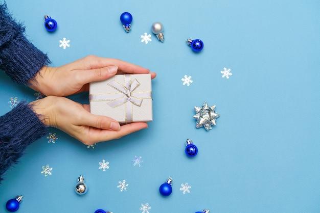 As mãos da mulher segurando uma caixa de presente presente amarrada com um laço de fita sobre fundo azul ao redor da árvore de natal ...