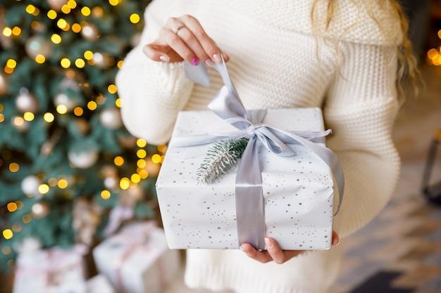 As mãos da mulher segurar a caixa de presente de natal ou ano novo decorado