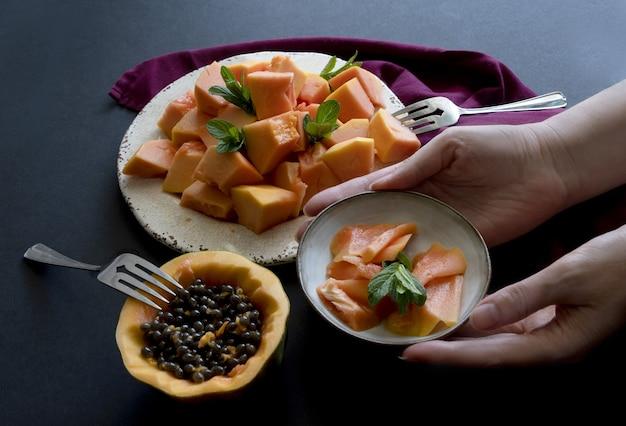 As mãos da mulher servem pratos com frutas fatiadas de mamão no prato