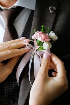 As mãos da noiva ajustam a flor na lapela da jaqueta de casamento do noivo