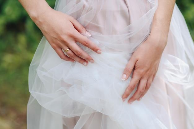 As mãos da noiva graciosa tocar tule em um vestido de noiva