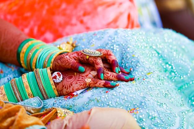 As mãos da noiva são lindamente decoradas pela arte indiana mehndi, juntamente com joalherias