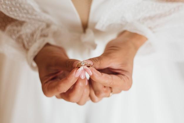 As mãos da noiva seguram o anel de noivado minimalista com pedras preciosas, fecham-se, sem rosto