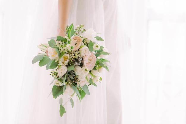 As mãos da noiva seguram um lindo buquê de rosas brancas.