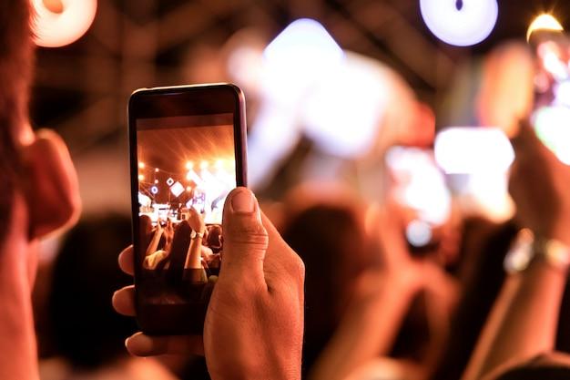 As mãos da platéia multidão pessoas tirando foto com o telefone móvel esperto em concerto de festa.