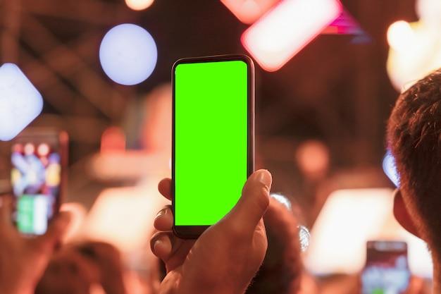 As mãos da platéia multidão pessoas tirando foto com telefone móvel esperto com tela verde em concerto de festa.