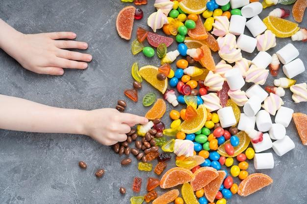 As mãos das crianças alcançam os doces que estão sobre a mesa.