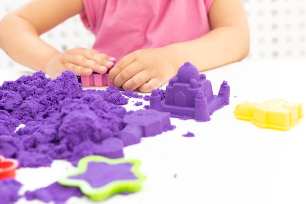 As mãos das crianças brincam com areia cinética em quarentena. areia roxa em uma mesa branca. pandemia do coronavírus