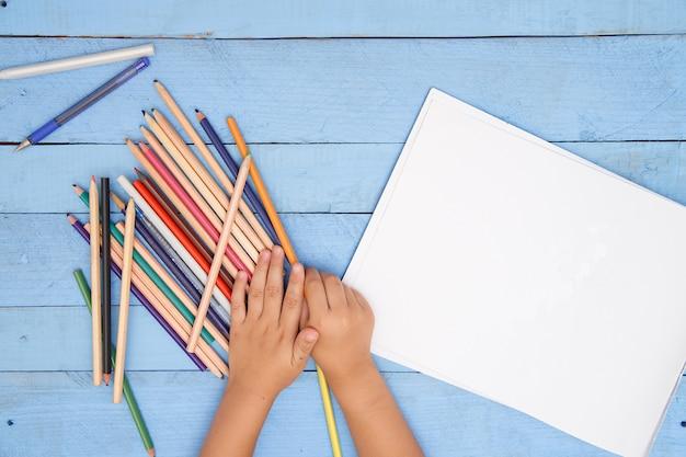 As mãos das crianças desenhar com lápis no álbum na mesa azul