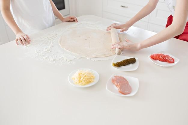 As mãos das crianças desenrolar a massa de pizza em uma mesa branca. se divertindo juntos na cozinha. vista de cima.