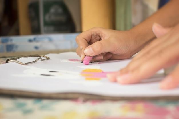 As mãos das crianças estão desenhando e colorindo em papel branco