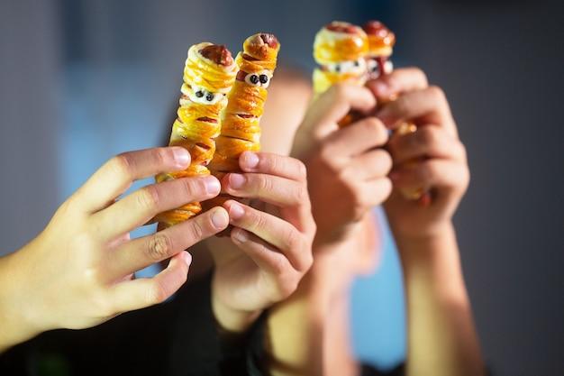 As mãos das crianças estão segurando lanches de halloween em forma de múmia, feitos de massa e salsicha