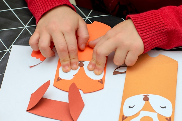 As mãos das crianças fazem artesanato de papel de natal