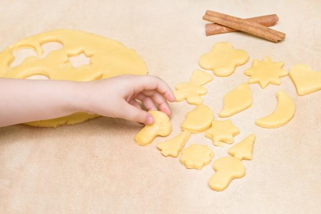 As mãos das crianças fazem biscoitos de natal