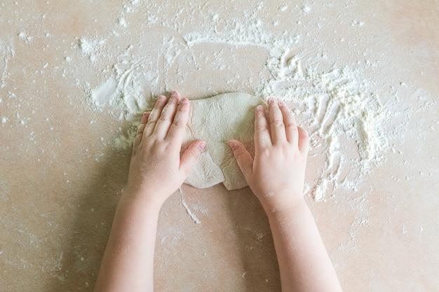 As mãos das crianças fazem massa