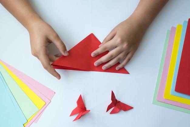 As mãos das crianças fazem origami uma borboleta.
