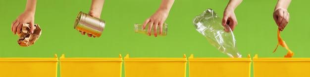 As mãos das crianças jogam papel, metal, vidro, plástico e lixo orgânico em diferentes recipientes amarelos em uma parede verde clara. triagem de resíduos. cuidado com o meio ambiente. reciclagem e conceito de ecologia.