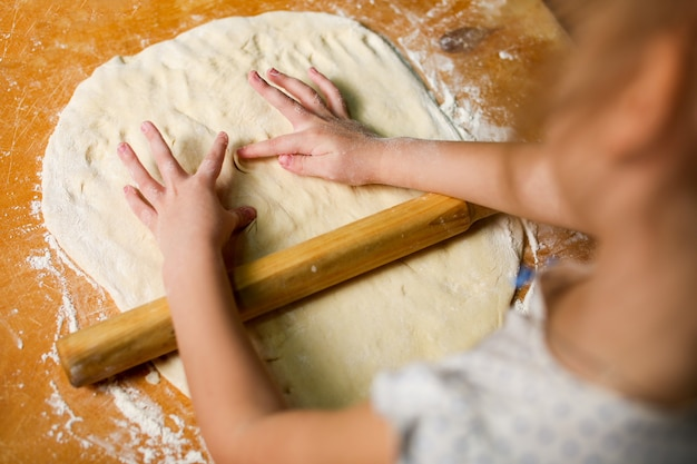 As mãos das crianças na massa, esculpem as impressões das mãos.