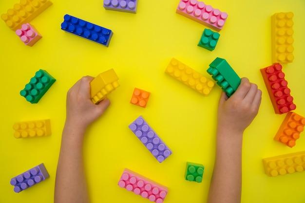 As mãos das crianças seguram os detalhes do construtor em um fundo amarelo.