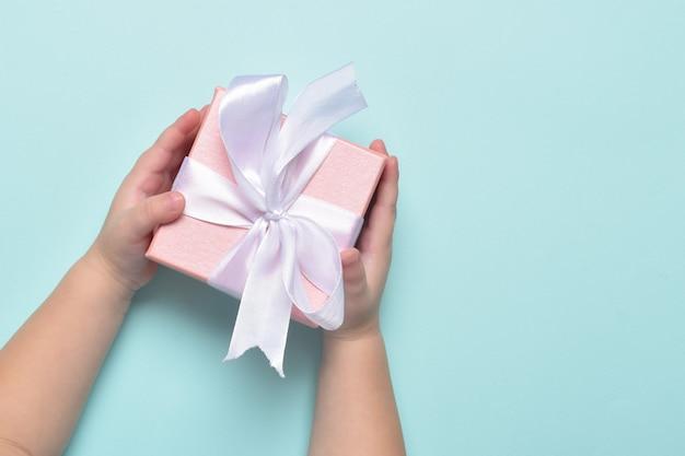 As mãos das crianças seguram um presente rosa com um laço branco sobre um fundo azul. feliz aniversário, feliz dia das mães.