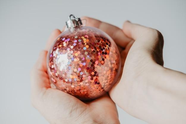 As mãos das crianças seguram uma bola vermelha e brilhante de ano novo, close-up. conceito de celebração familiar para o natal e ano novo.