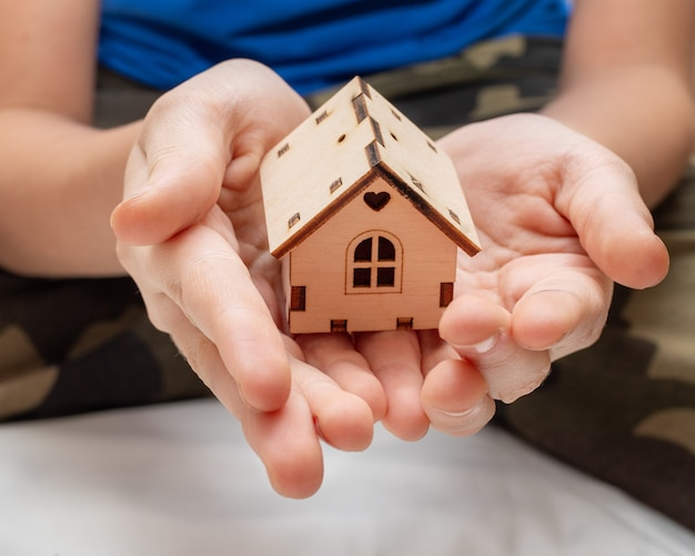 As mãos das crianças seguram uma pequena casa de madeira. um símbolo de família, conforto do lar, doce lar.