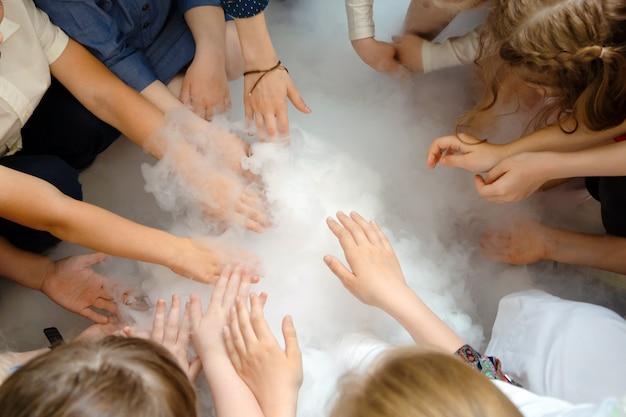 As mãos das crianças tocam a fumaça do nitrogênio líquido.