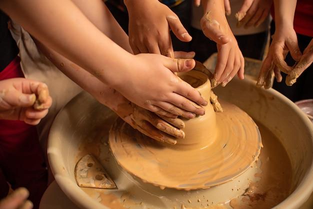 As mãos das crianças trabalham com argila em uma máquina especial. produtos de barro
