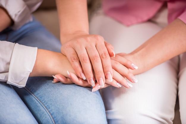 As mãos das meninas encontram-se em seus joelhos e prendem sua segunda mão.