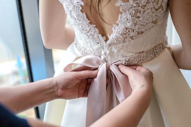 As mãos das mulheres amarram o laço no vestido de noiva