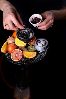 As mãos das mulheres colocar tabaco de frutas em um narguilé em um fundo preto