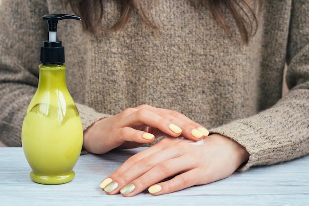 As mãos das mulheres com manicure amarelo aplicaram o creme para as mãos