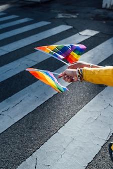 As mãos das mulheres com uma bandeira do orgulho gay