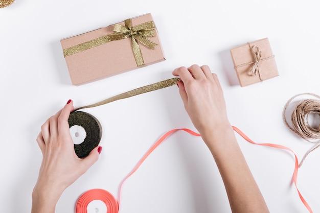 As mãos das mulheres com uma manicure vermelha preparam presentes em caixas para o feriado