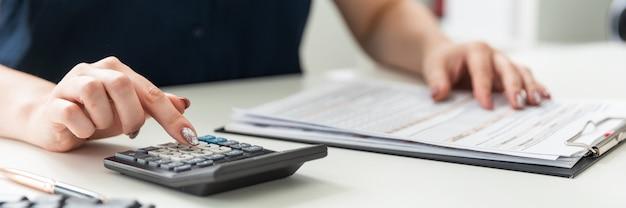 As mãos das mulheres contam com a calculadora e preenchem o formulário.