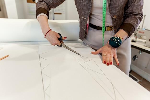 As mãos das mulheres cortam o padrão de papel com uma tesoura de alfaiate em uma mesa branca. pano, mãos, costura, design