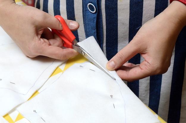 As mãos das mulheres cortam o tecido com uma tesoura de acordo com o padrão na mesa.