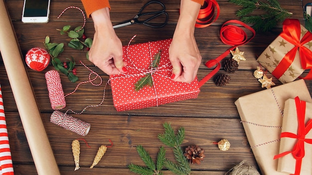 As mãos das mulheres decoram a caixa de presente. composição de natal contra um fundo escuro