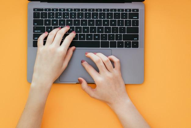 As mãos das mulheres digitam o texto no teclado do laptop na superfície laranja
