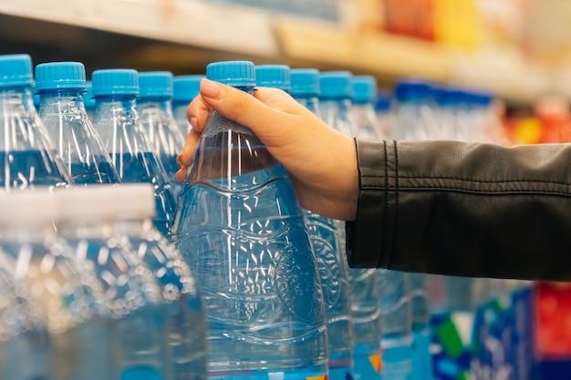 As mãos das mulheres do close up prendem mantimentos na loja. o conceito de compra de frutas e legumes em um hipermercado durante quarentena