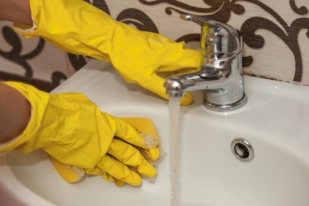As mãos das mulheres em luvas de borracha amarela lavam o lavatório no banheiro. close da pia de limpeza. limpeza e ordem na casa. conceito de conforto doméstico ou serviços de limpeza