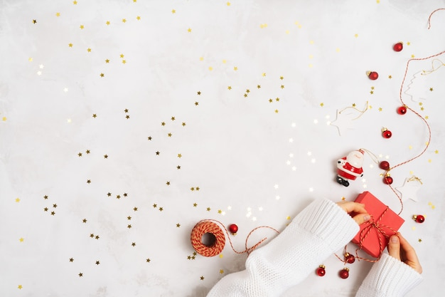 As mãos das mulheres em um suéter embalam uma caixa de presente para o ano novo. decoração criativa de natal em fundo branco com confete
