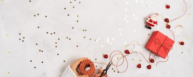 As mãos das mulheres em um suéter embalam uma caixa de presente para o ano novo. decorações de natal criativas em fundo branco com confete
