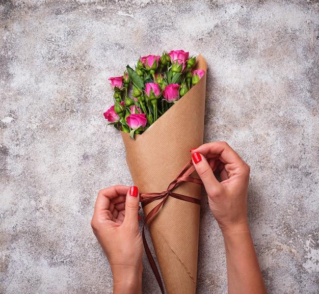 As mãos das mulheres embrulhar um buquê de rosas em papel Foto Premium