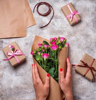 As mãos das mulheres embrulhar um buquê de rosas em papel