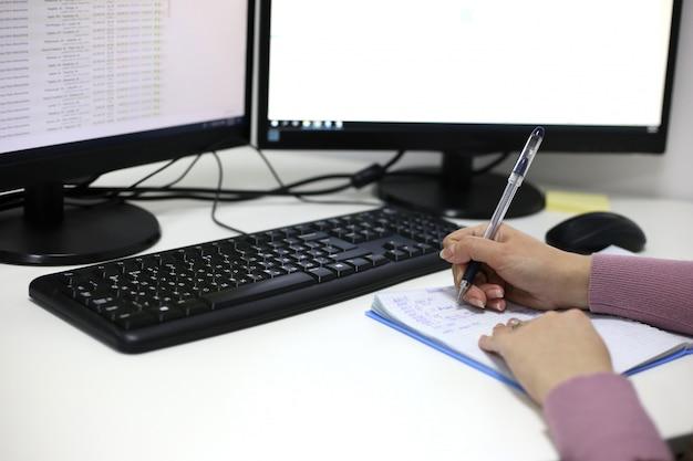 As mãos das mulheres escrevem em um notebook contra um monitor de computador